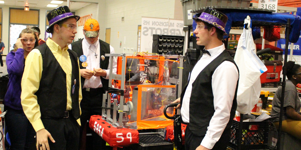 Two men with matching hats in front of a robot.