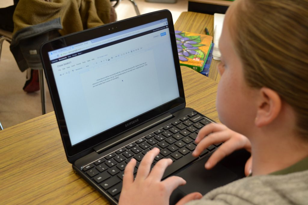 Student typing on computer.