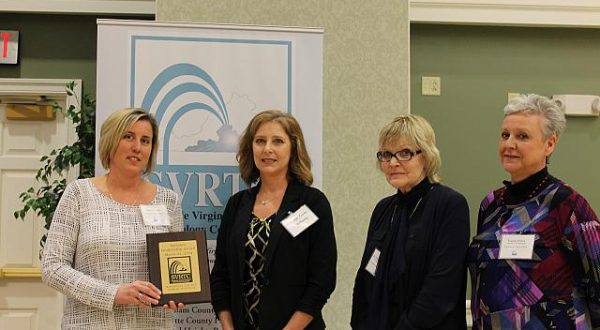 Four women standing with an award.